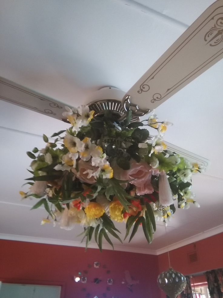 just finished making this lampshade to cover ugly lights on fan. Used old fan cover and artificial flowers.