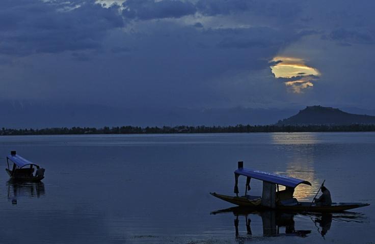 Srinagar, Jammu und Kashmir, 12. April 2012:  Rätselhafte Stimmung an einem regnerischen Tag am Dal-See im indischen Bundesstaat Jammu und Kashmir. Durch ein Loch in der Wolkendecke scheint ein letzter Rest des Tageslichts auf den See.