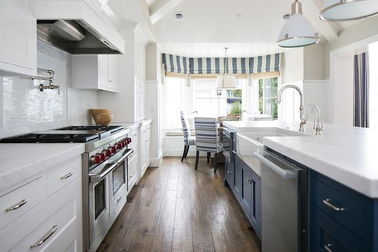 White and blue kitchen features white shaker cabinets paired with Pacific White Marble countertops and backsplash.