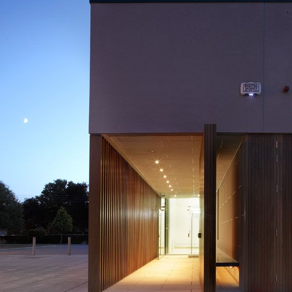 Large timber pivot door signifies the centre is open. One enters into a lower entrance space before turning right into the taller entrance area. Open timber fins on the left allow for movement of light, the bench, with a window under allows for a place to sit and for those inside to see movement.