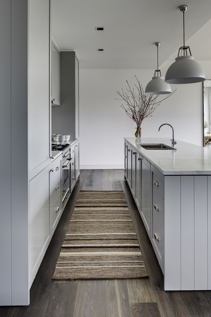 Pale pastel blue-grey Shaker kitchen cabinets, brushed silver chrome handles, marble benchtops, chrome mixer gooseneck tap, two light grey pendant lights over island, cherry blossom stems in glass vase, timber floorboards