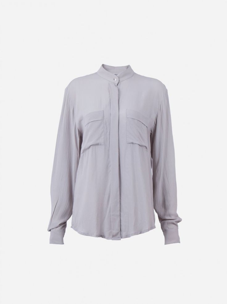 A very relaxed and comfortable loose shirt made of rayon fabric. Features long sleeves, hidden button front, skinny high collar, and front pockets.