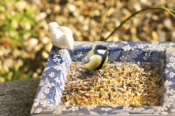 Szögletes kerámia madáritató kék-fehér virágos mintával, fehér madárral.