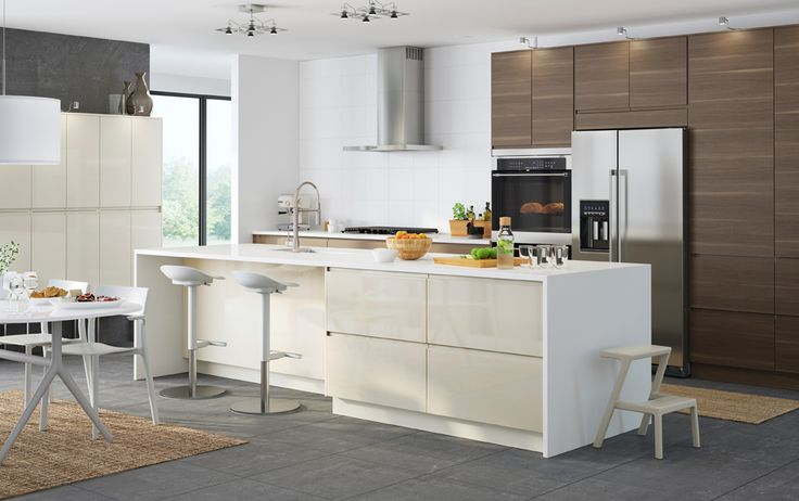 A large kitchen with light beige high-gloss doors and drawers combined with walnut effect doors and drawers. Shown together with stainless steel appliances.