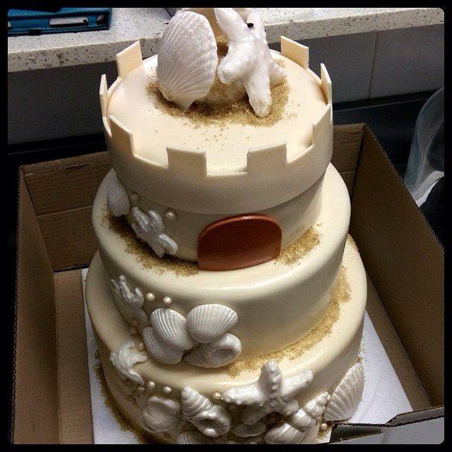 Sand castle wedding cake for a beach wedding.
