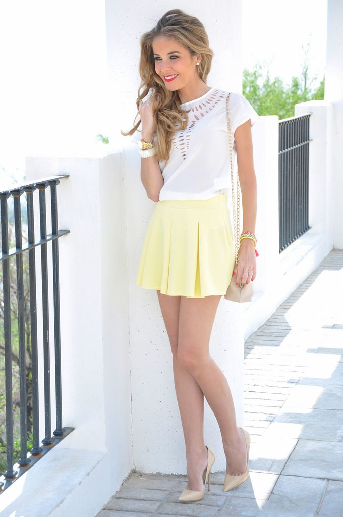 Summer looks. Yellow mini skirt, white blouse and heels.