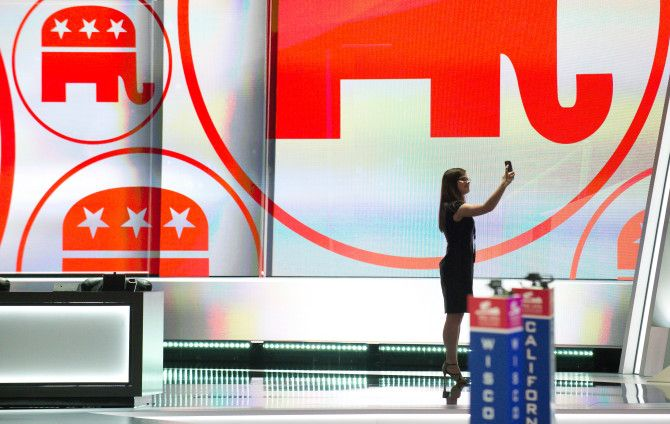 A woman takes a selfie from the stage as preparations get underway for the Republican National Convention at the Quicken Loans Arena in Cleveland, Ohio on July 17, 2016. An estimated 50,000 people are expected in Cleveland, including hundreds of protesters and members of the media. The four-day Republican National Convention kicks off on July 18.