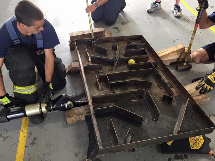 A maze that firefighters have to maneuver so a ball gets from the starting point to the end. This provides an opportunity to put different tools in the hands of some firefighters.