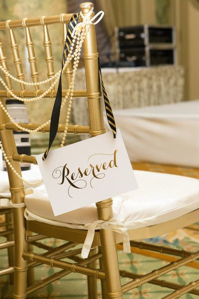 "White + gold wedding chair decor idea - white sign with ""reserved"" written in metallic gold calligraphy hanging on metallic gold chiavari chair {Photography by Marirosa}"