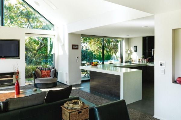 The kitchen and living area feature natural colours, simple furnishings and extensive glazing that provides ...