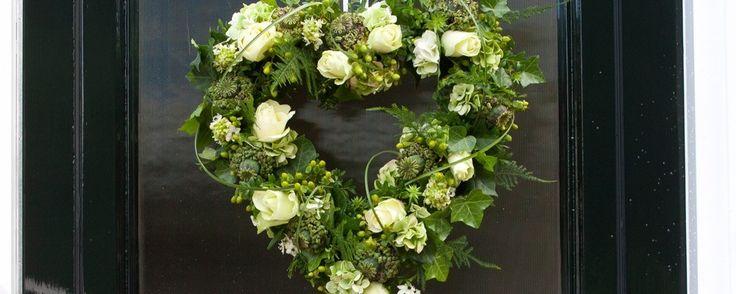 mooi voor huis van de bruid Een hart aan de deur, potten versierd met linten, ringen aaneen 'gesmeed' tegen de gevel of het tuinhek. De boodschap is duidelijk: hier wordt getrouwd en dat mag iedereen weten! Ook de mand en krans met witte rozen passen perfect bij een trouwerij.