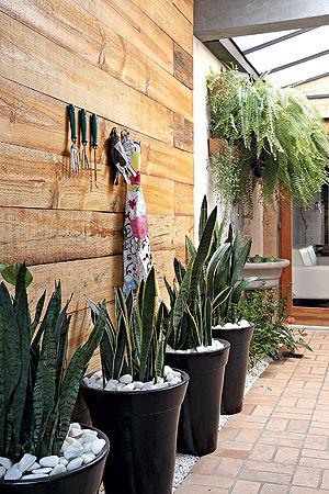 O corredor do jardim de inverno recebeu o painel de pínus escurecido, onde foram pendurados o avental da Zona D e os acessórios da Verde Vaso. Nos vasos, espadas-de-são-jorge. Ao fundo, samambaias criam uma cobertura natural