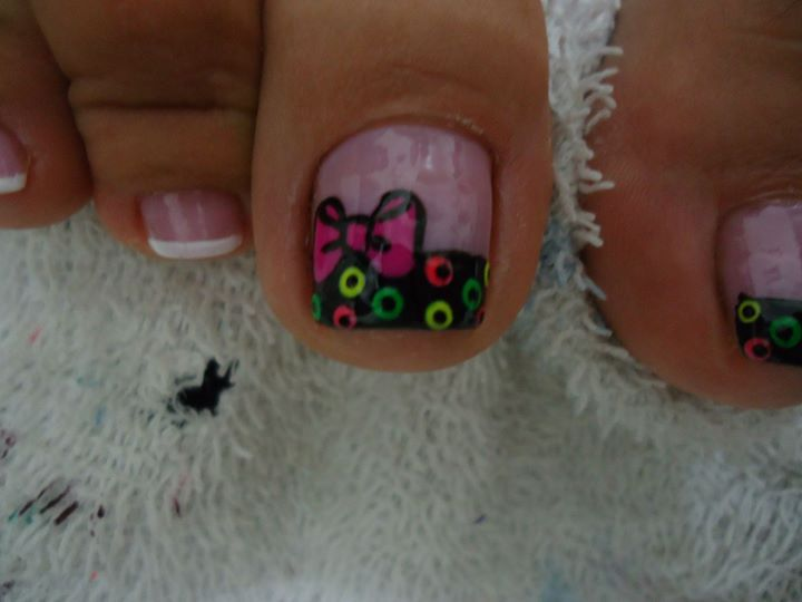 decoración de uñas de los pies  con un moño rosa y puntos de colores