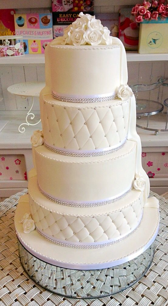 A gorgeous 4 tier classic wedding cake with a touch of bling and handcrafted roses with quilted separate tiers