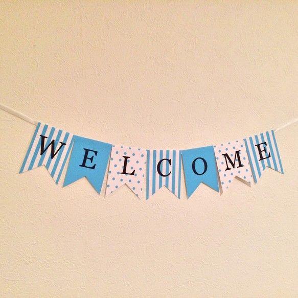 結婚式やパーティーなどにぴったりのガーランドです(^ ^)「WELCOME」の8文字。色はティファニー風ブルー♡ストライプ、単色、ドットの3つのパターンが並びます。ポップだけどポップ過ぎず、爽やかでおしゃれな雰囲気に仕上がりました♪また、サムシングブルーという言葉があり、結婚式にブルーのものを使用するのは縁起がいいとされています(^ ^)左右のリボンは用途にあわせて長さを調節してご利用ください。幅6mmの白色のリボンがついています。ガーランドの1文字(1枚)のサイズは、縦10.5cm×横7.5cmです。厚さは官製はがき程の厚さです。結婚式の受付や、ウェルカムスペース、ウェルカムボードなどにぜひご利用ください。手で持って前撮りなどの写真撮影に使うのもおすすめです!