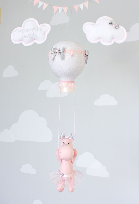 Baby Mobile a hot air balloon and floating hippo nursery decoration for a travel theme girls nursery. Blush Pink and Gray baby mobile. She is floating off on an adventure with her tiny tutu thats finished with a big gray bow that matches the one on her head and the balloon above. Tiny little eyelashes were added for the perfect girly touch. The blush pinks and light gray fabrics are a great addition to your nursery.  As with all my designs, they can be customized to match your nursery décor…
