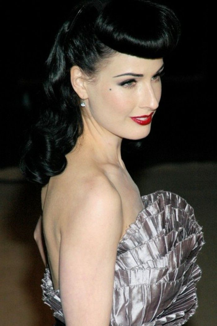 pinned up hairstyles for long hair, dita von teese, black hair with bettie bangs, red lipstick and white teeth, mascara eyeliner and a beauty spot, nude shoulders and a shiny dress with ruffles