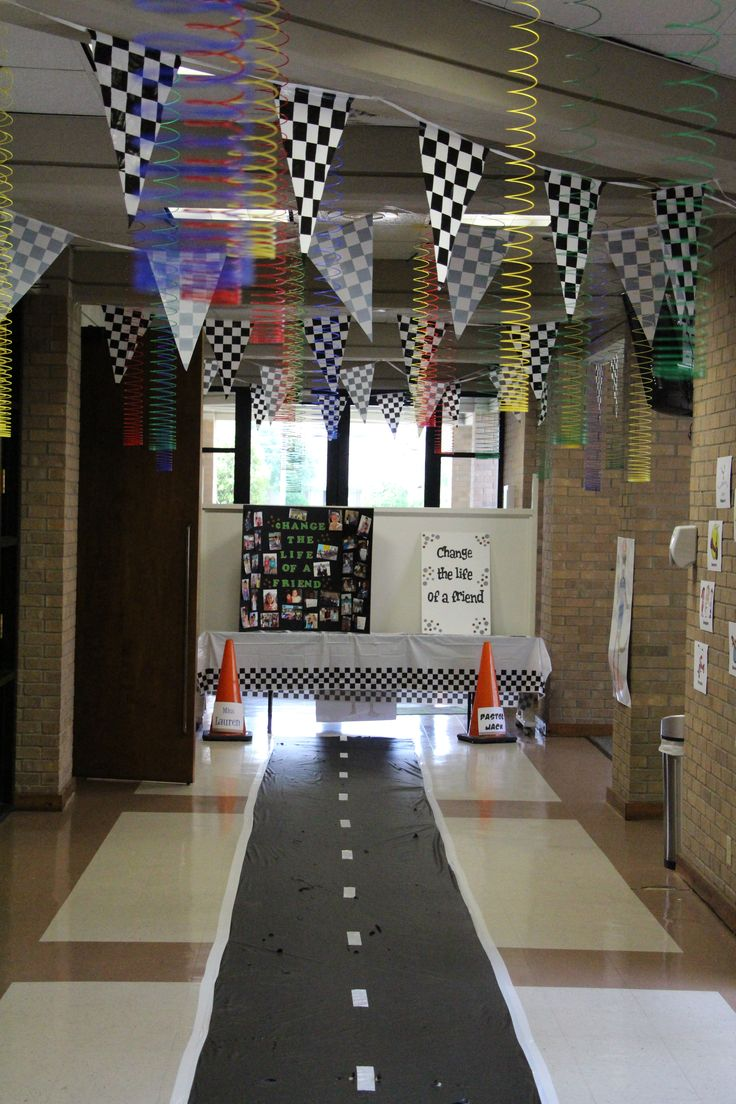 """Fuel up for G-Force VBS with some of these ideas! Black trash bags and white duct tape create the floor. Checkered flags add depth and the Slinky's are just plain ole fun! Cones work well too! Are you """"seeing"""" G-Force through these decorations? Ready Set Go!  (Landscape fabric and white duct tape last longer than these trash bags.)www.cokesburyvbs.com"""