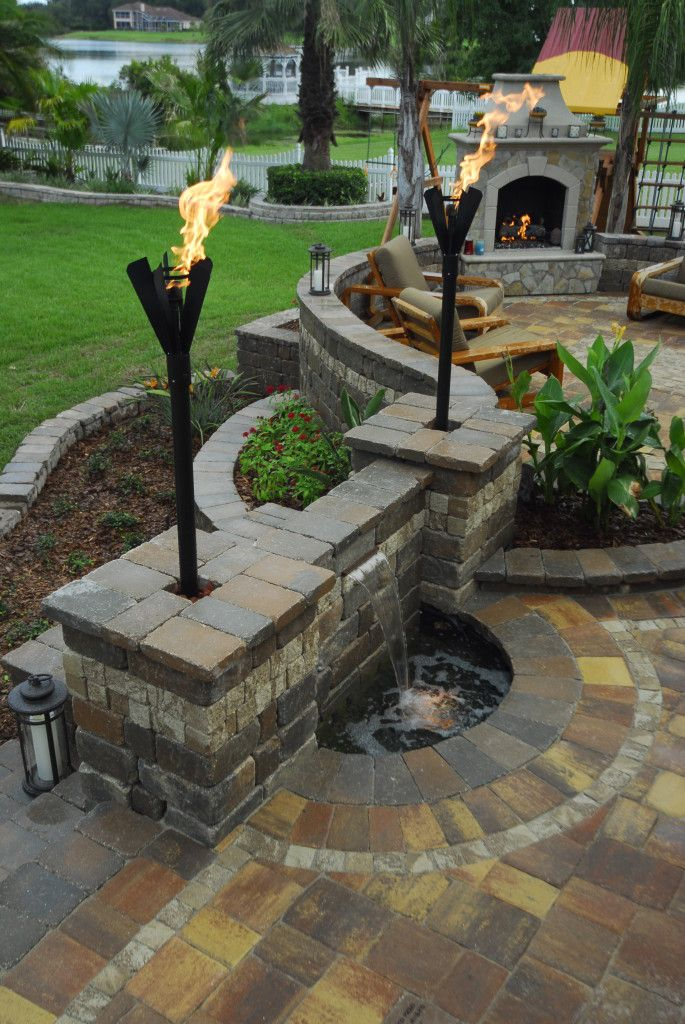 Beautiful back patio. Water-feature, fireplace & nice touch with the torches.