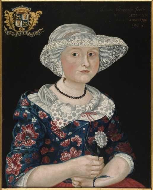 Thomas Gonggrijp - Schilderij, portret van Jetske Gonggrijp. VervaardigerGonggrijp, Thomas TrefwoordenGonggrijp, Jetske ObjectnummerFSM-G-153 Periode van1749 Periode tot1749 BeschrijvingPortret en trois quart, ten halve lijve, zittend. De geportretteerde is Jetske Gonggrijp. Ze is gekleed in een gebloemd sitsen jak, ze draagt een slingerdoek en een kanten luifelmuts (Duitse muts). In de rechterhand een witte anjer.