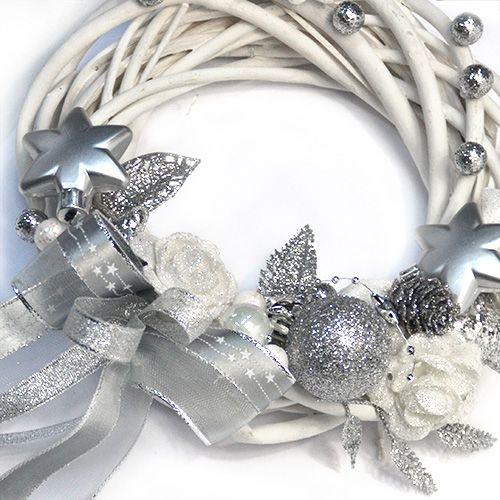 Vánoční věnec ve stříbrné a bílé barvě Vánoční dekorační věnec zdobený třpytivými bílými a stříbrnými dekoracemi, proutěný korpus v bílé barvě, na věnci je připravené poutko pro zavěšení na dveře. Průměr věnce je 20 cm.