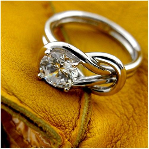 """Breathtaking """"knot"""" design ring, symbolizing a union of two. Great gift for engagement, wedding and friendship…….. Topped with AAA high quality round stone in prong setting."""