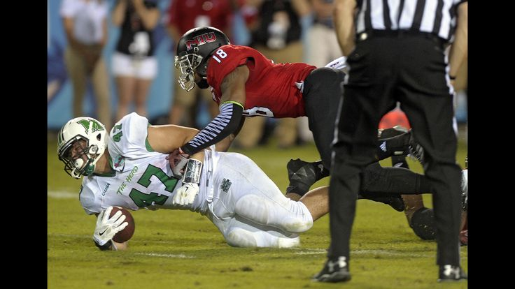Boca Raton Bowl  Marshall running back Devon Johnson gains a first down while being tackled by Northern Illinois University linebacker Bobby Jones IV, Tuesday, December 23, 2014, at FAU Stadium.  http://www.sun-sentinel.com/sports/sfl-boca-raton-bowl-pictures-20141223-034-photo.html