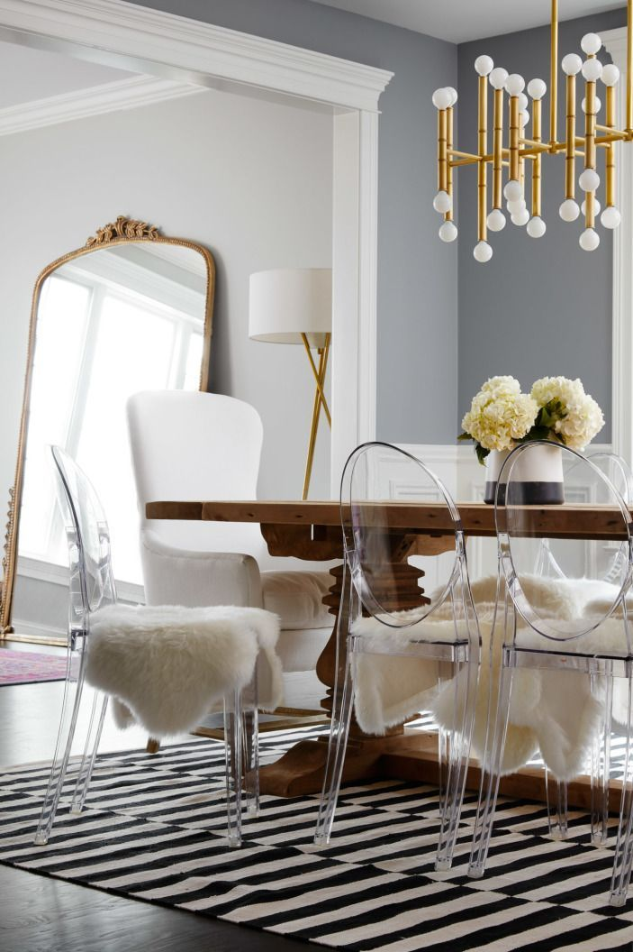 "The dining table is surrounded by fur-covered Lucite chairs. Though they look absolutely chic, the chairs have a functional purpose. (It's easy to clean off little handprints from the clear surface.) Laura unabashedly admits, ""In spite of having a kitchen and dining room I love, we get take-out or eat out almost every day."""