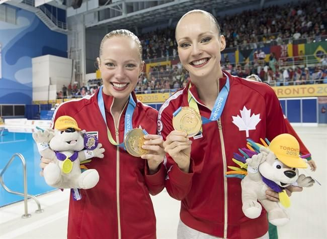 Jacqueline Simoneau (Saint-Laurent, Quebec) and Karine Thomas (Gatineau Quebec), right, of Canada show off their Gold medals after winning the Synchronized Swimming Duet at the 2015 Pan Am Games in Toronto on Saturday, July 11, 2015. THE CANADIAN PRESS/Frank Gunn