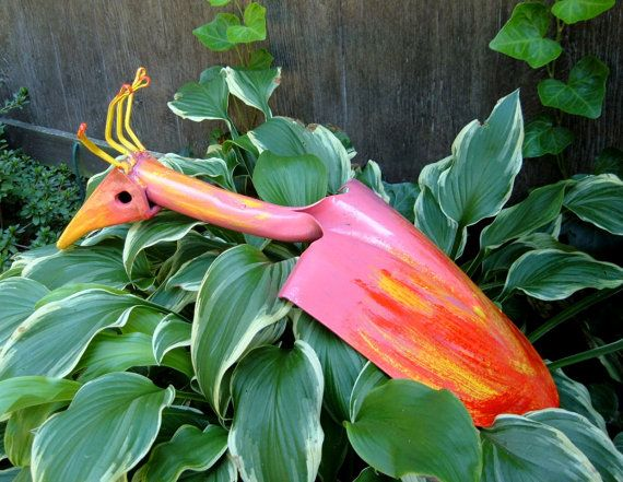 Pink Tropical Bird from an old  shovel and a loose tooth from an excavator bucket.    The legs are designed to be the stakes that support her  in the ground. Hand painted with industrial oil base enamels  for durability and shine.