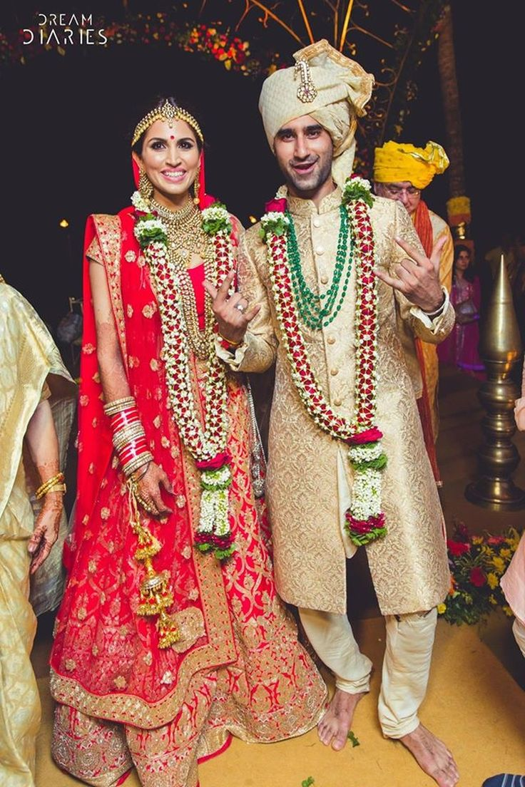 Khushi and Sam dressed in complementing gold and red outfits for wedding ceremony held at Grand Hyatt, Goa