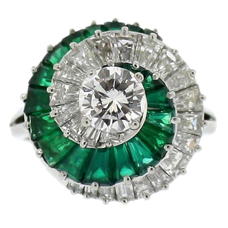 Emerald and diamond spiral ring by Cartier. Set to the centre with a round brilliant cut diamond raised in a four claw setting with a weight of 0.85 carats, encircled by a swirled row of twenty two channel and claw set tapered baguette cut diamonds weighing 3.00 carats in total, adjacent to a stepped corresponding row of twenty channel and claw set tapered baguette cut emeralds with an approximate weight of 3.00 carats. The approximate total diamond weight is 3.85 carats. The head has…