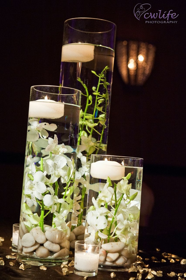 Submerged delicate orchids with river rocks and candles