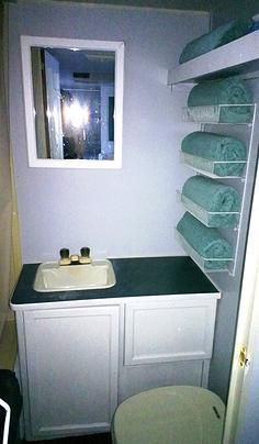 I like the towel storage idea....Camper mini bathroom redo in grey and aqua.