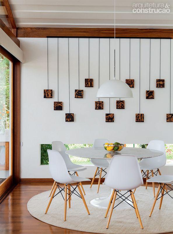 Casa incorpora árvore no deck e se beneficia de sua sombra_Um rasgo de vidro deixa entrever o exterior na sala de jantar. Cadeiras da Tok & Stok e lustre da reka. Na parede, matrizes de xilogravura de J. Borges.