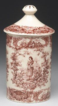 Canister 9 1/2In Red by Nutiques. $35.00. Red and white transferware porcelain with Joan of Arc inspired design all around with floral border and trim that has courtship scene inserts. Lid is removable. (pc)