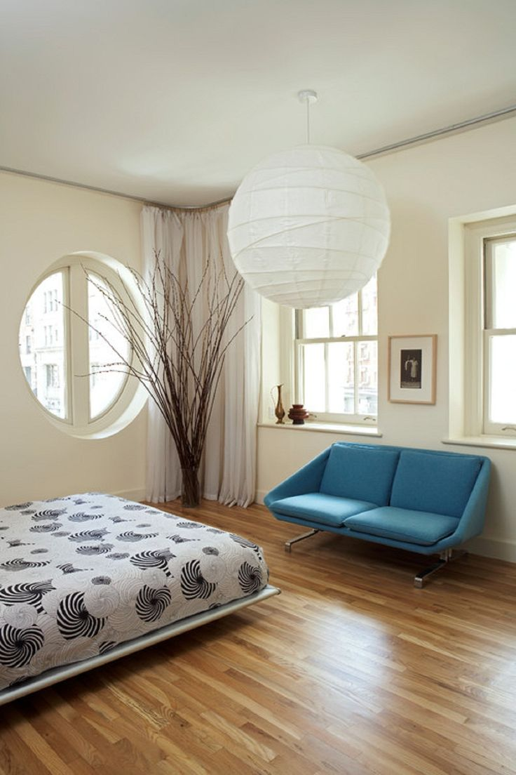 Minimalist Bedroom With Round Window And White Globe