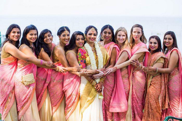 South Indian bride. Gold Indian bridal jewelry.Temple jewelry. Jhumkis. White silk kanchipuram sari with multicolored blouse.Braid with fresh jasmine flowers. Tamil bride. Telugu bride. Kannada bride. Hindu bride. Malayalee bride.Kerala bride.South Indian wedding. Bridesmaids saris.