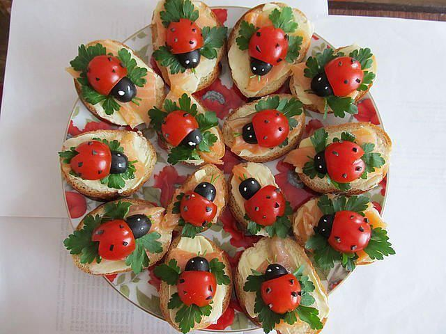 Cherry tomatoes and black olives make really cute lady birds. Base is made up of sliced bagettes, cream cheese, smoked salmon and flat leafed parsley. Sprinkle ground black pepper on tomato and using a toothpick dot some cream cheese on the olives for the eyes.