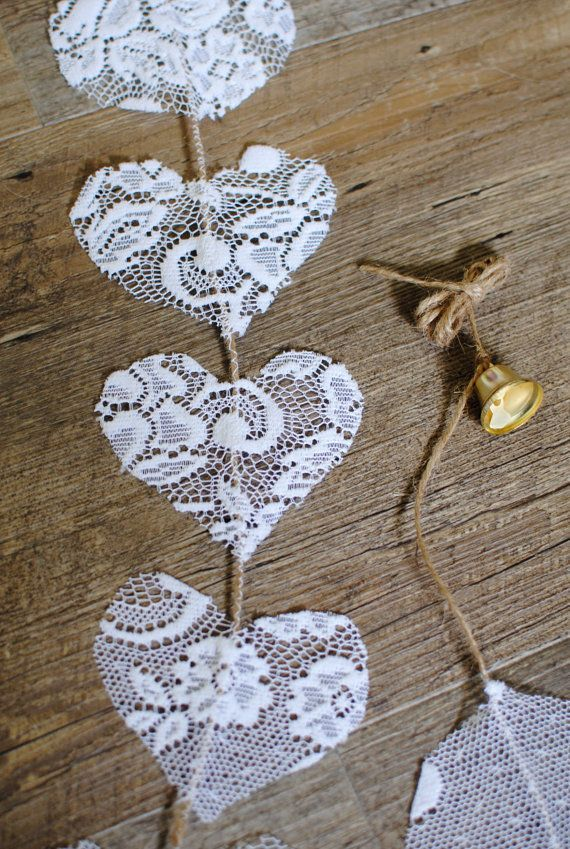 Vertical lace hearts on a jute cord, with a gold coloured bell. Suitable to decorate wedding and party venues.
