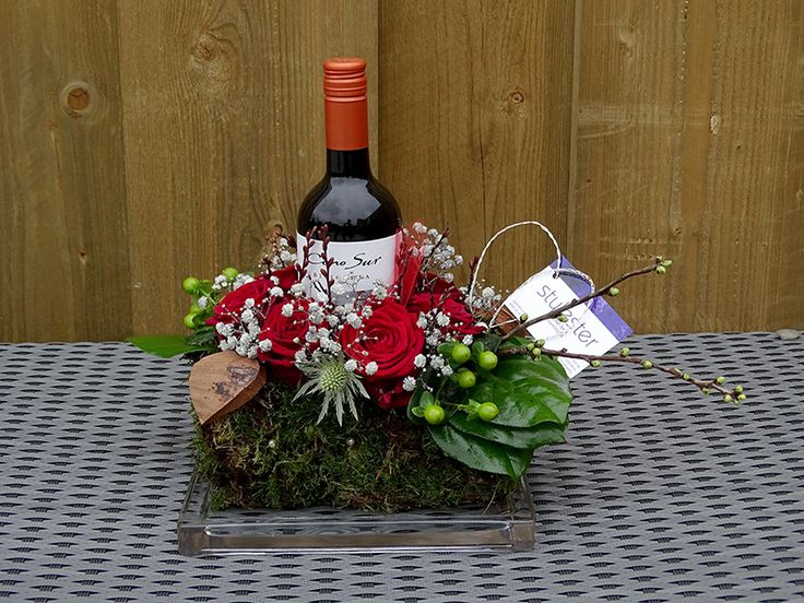 Jubileumcadeu met rode (baccara) rozen. Gedecoreerd met rode wijn.