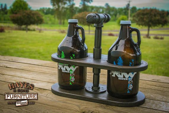 Rustic Industrial Beer Growler Caddy from Hayes & Sons Furniture This unique rustic caddy holds two standard-sized beer growlers. Perfect for any gift! Made from 3/4 Black Iron Pipe and Maple Plywood (painted Black Night). These caddies come collapsed for easy shipping. With a simple