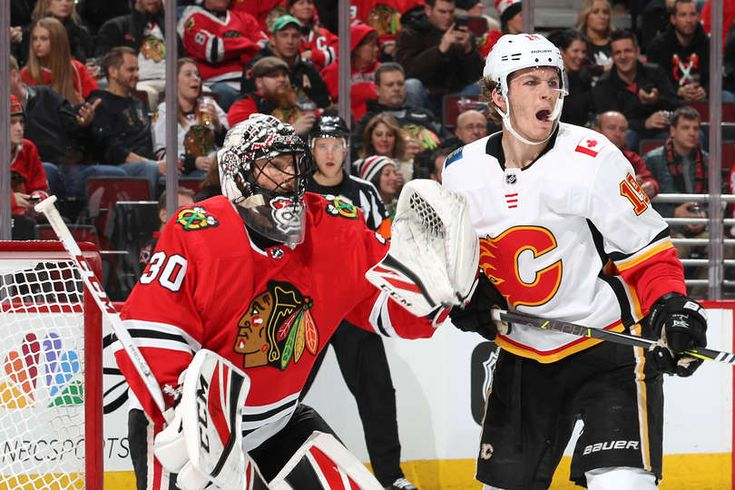 CHICAGO, IL - FEBRUARY 06: Matthew Tkachuk #19 of the Calgary Flames stands in position next to goalie Jeff Glass #30 of the Chicago Blackhawks in the third period at the United Center on February 6, 2018 in Chicago, Illinois. (Photo by Chase Agnello-Dean/NHLI via Getty Images)