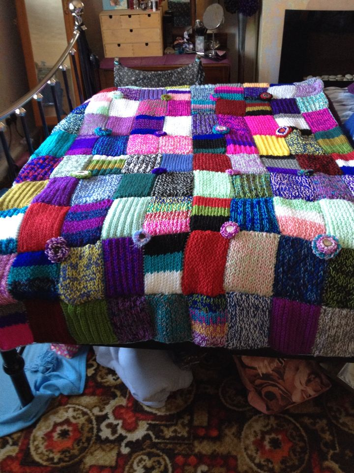 Loom knitted blanket made of 100 different rectangle panels each different, with loom knitted flowers in between.
