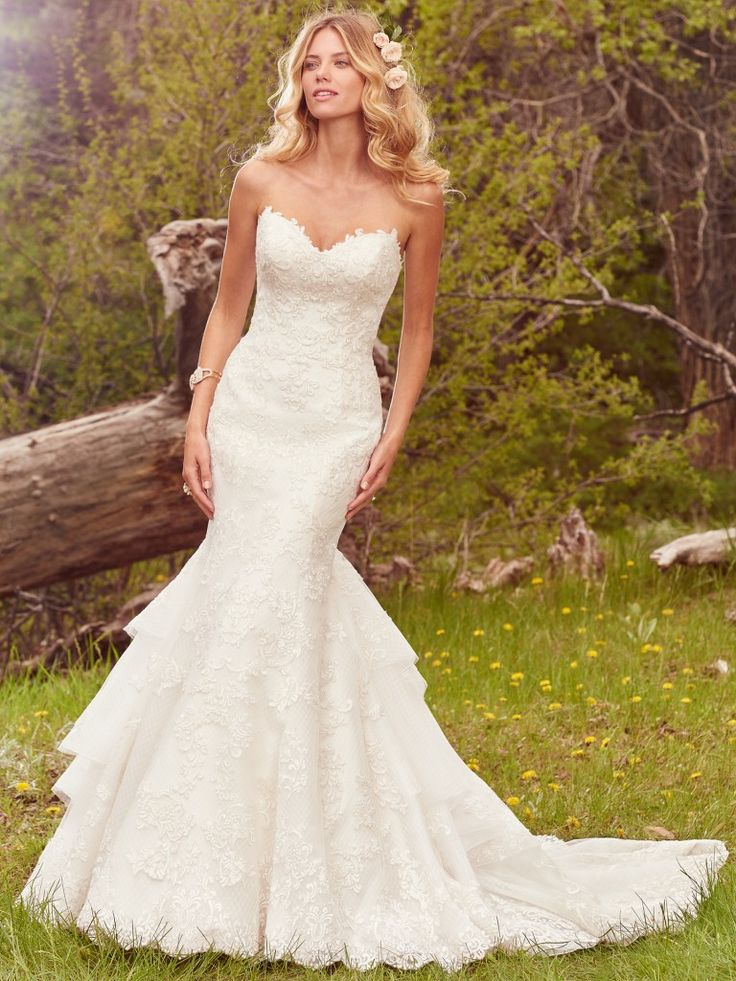Maggie Sottero - GOLDIE, This glamorous fit-and-flare features a layer of lace motifs atop crosshatched tulle, complete with a gorgeous layered train and strapless sweetheart neckline. Finished with crystal buttons over zipper and inner corset closure.