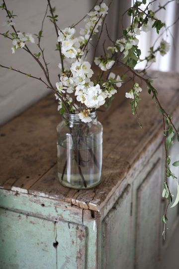 Blossoms in a jar | Photo by Simon Griffiths --- Hanging mason jar vases w/antiqued wood backing on great room wall