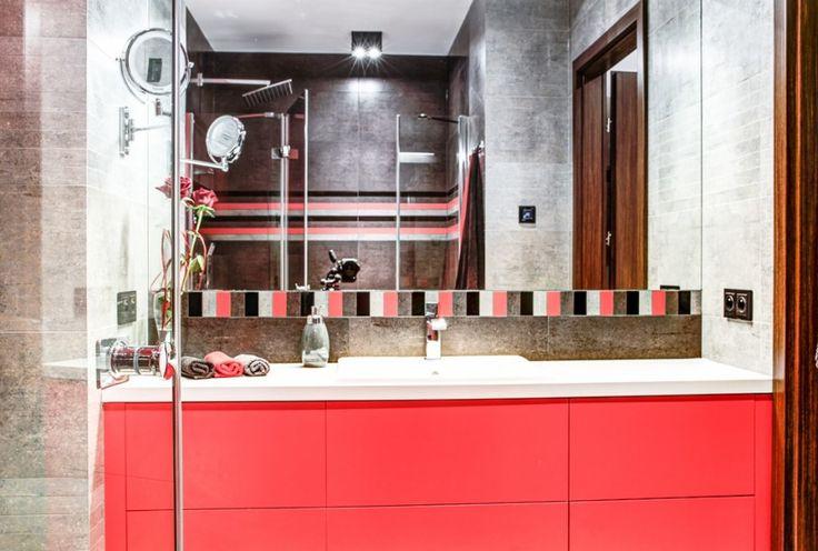 Wnętrze łazienki wykończone w nowoczesnym stylu, z płytkami w szarym kolorze uzupełnione czerwonym motywem pasków. Do tego intensywna czerwona szafka pod umywalkę i duże lustro, które wbrew pozorom tworzą jasne i przestronne wnętrze.