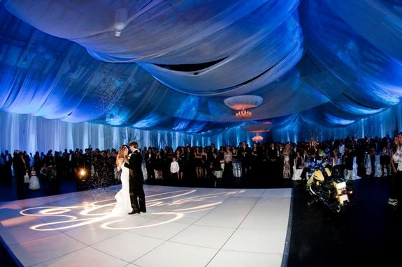 Blue ceiling draping at a winter wonderland, ice blue wedding | Featuring Tiffany white and Tiffany platinum linens, silver trees with hanging crystals and clear acrylic dining chairs | Linen Effects - Minneapolis, MN | Linen, table top decor and chair cover rentals
