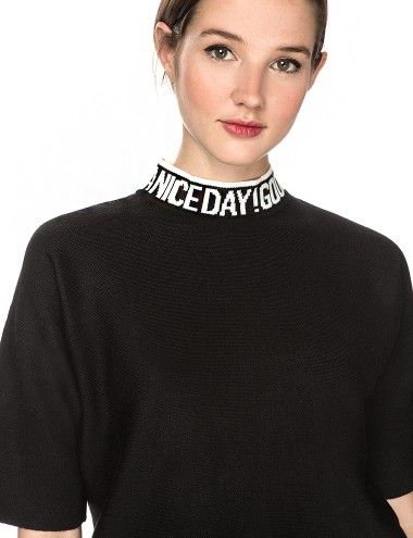 """You said it right there! Wear your heart on your sleeve with this super cool black knit short sleeve sweater, featuring """"Have a nice day! Good luck!"""" printed on collar with white ribbing."""