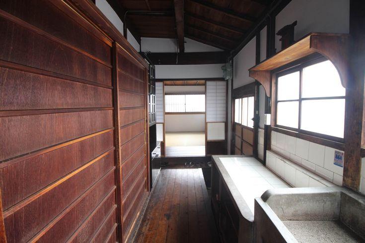 何度も磨かれたであろう板の艶、ガラス扉を閉める時のガラガラという心地よい音。 久しぶりに直感を刺激される物件に出会いました。 昭和初期に建てられたという京町家ですが、この度改装を経て借主を募集しています。改装済みの京町家はたくさんありますが、「あーそうそう、この程度で十分なんだよね」っという心地いい改装がされています。よく「こんな風に直したら台無し・・・」と思ってがっかりすることも多いのですが、この物件は大丈夫です。写真を見てもらってもわかる通りです。2階の広縁に古い机が置かれていましたが、もうこの空間だけでじわっときてしまいます。 間取りは6Kと、基本は建具で空間を仕切る形。ちゃんと玄関間もあります。縁側からは庭も望める様になっていてここに座りながら一杯やりたくなりますね。キッチン、というか台所はかつて使われていた石造りのまま。調理家電は持ち込まなければいけませんが、この雰囲気は変えがたい。気になるトイレ、バスルームも木のぬくもりを感じる形で改装されていて安心ですね。…